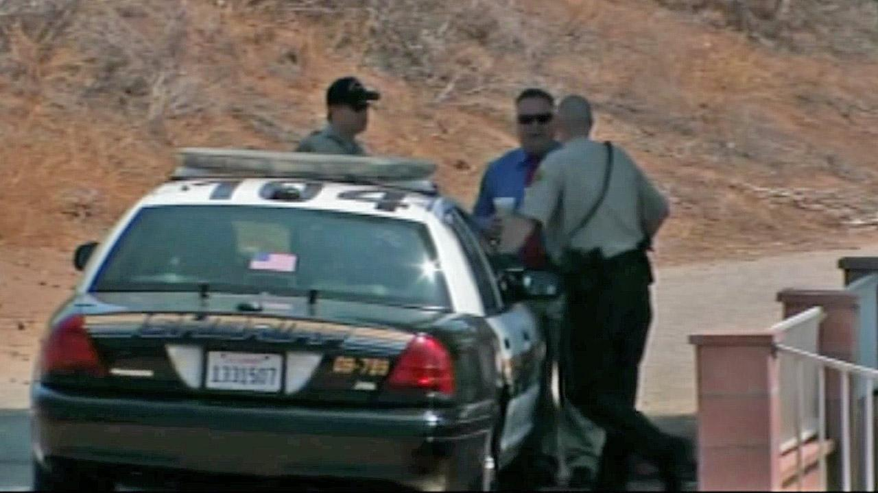 Investigators gather near a sheriffs patrol car near the scene of a deputy-involved shooting in Jurupa Valley on Saturday, July 14, 2012.