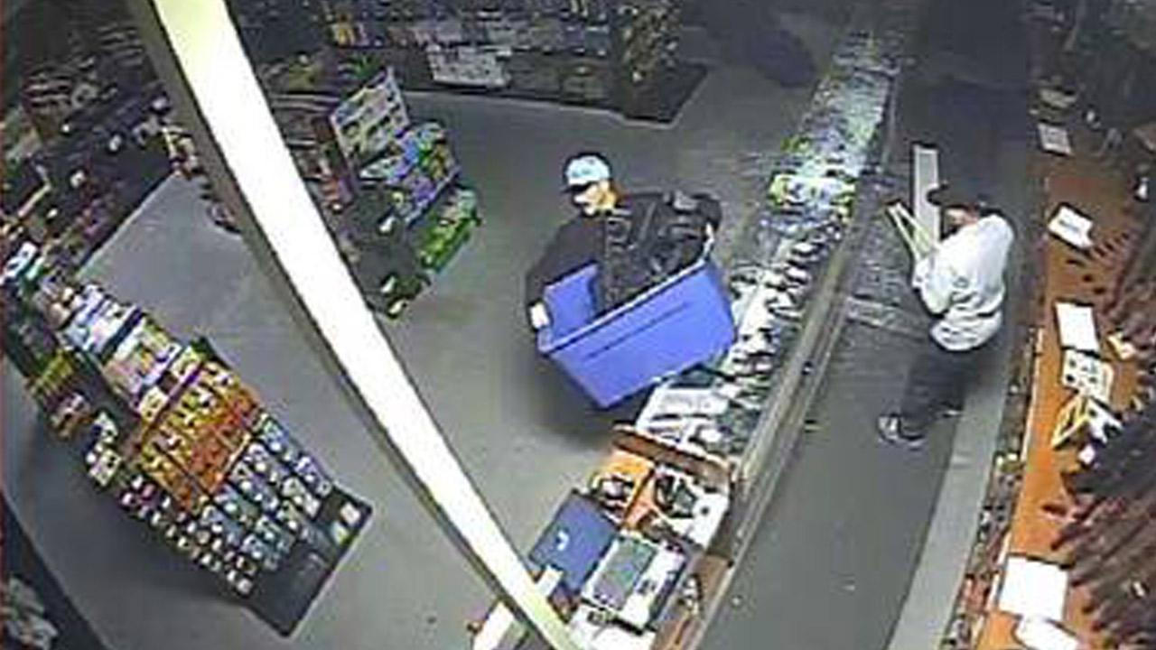 Suspects are shown stealing rifles from a Corona gun shop in this Aug. 14 surveillance image.