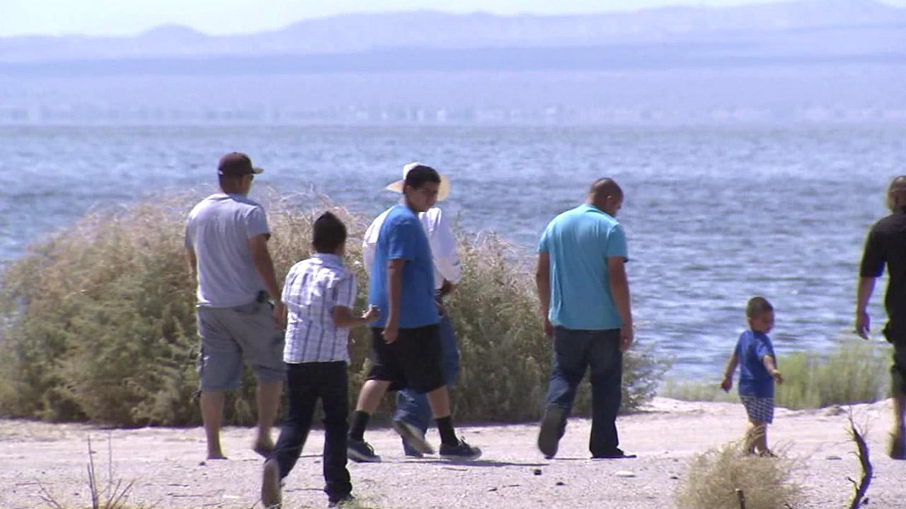 Visitors walk along the shore of the Salton Sea on Monday, Sept. 10, 2012.