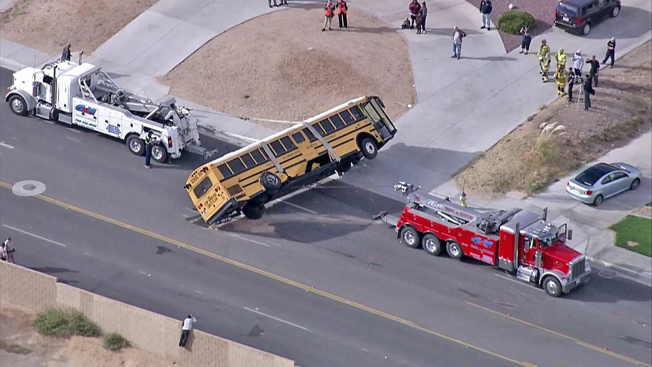Two big-rig tows are seen picking up a school bus after it crashed into a U-Haul truck while transporting 40 students from Galileo Academy in Victorville on Thursday, Oct. 11, 2012. The cause of the crash was not immediately known.