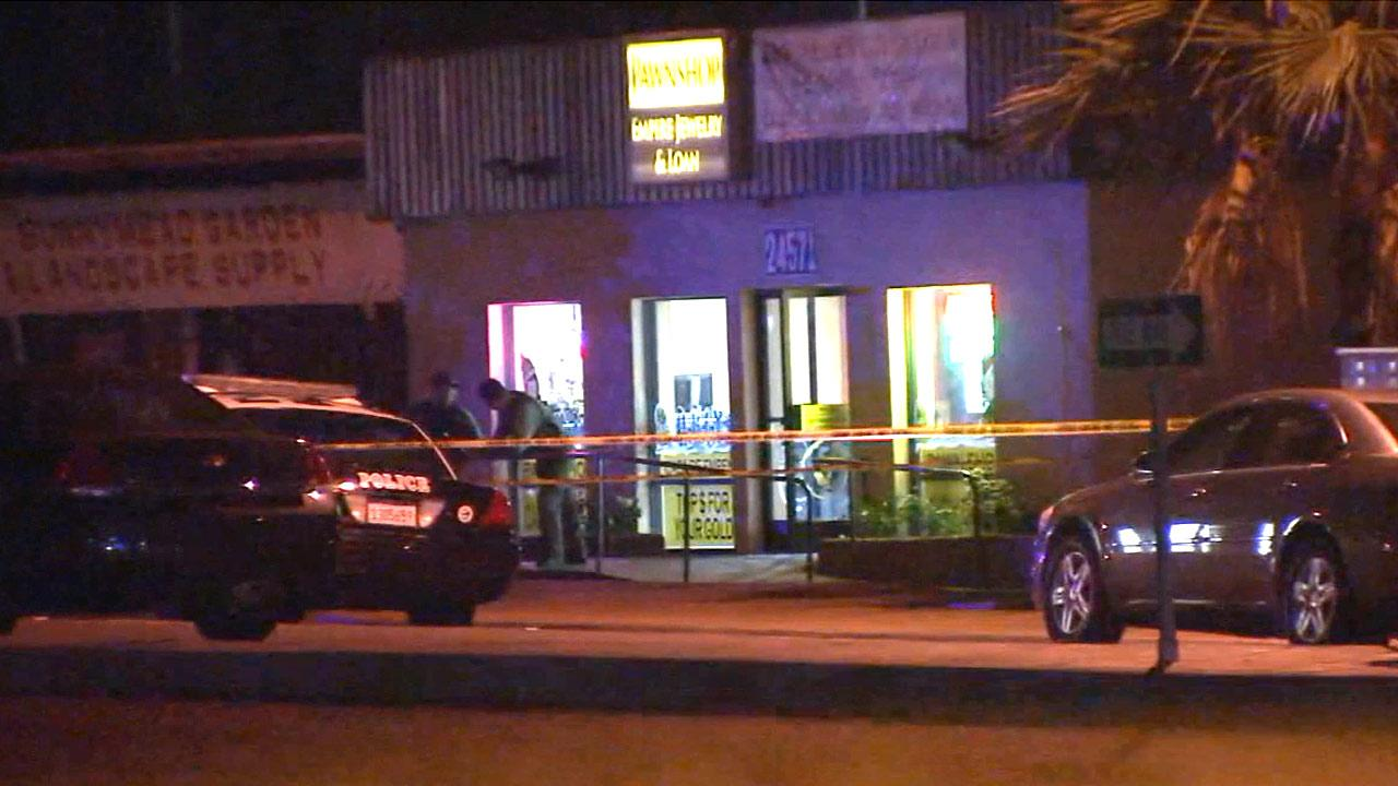 Authorities investigate an alleged robbery at shooting at a pawn shop in Moreno Valley on Wednesday, Dec. 12, 2012.