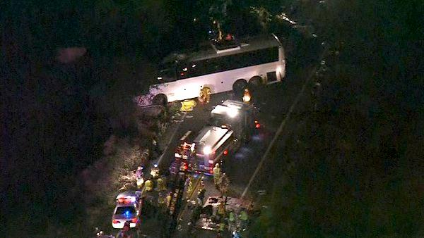 Rescue crews work at the scene of a deadly bus crash on State Route 38 north of Yucaipa on S