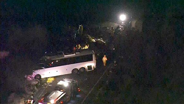 Rescue crews work at the scene of a deadly bus crash on State Route 38 north of Yu