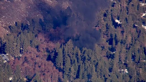 Smoke rises from a burning cabin in the Big Bear area where fugitive murder suspect Chris Dorner was believed t