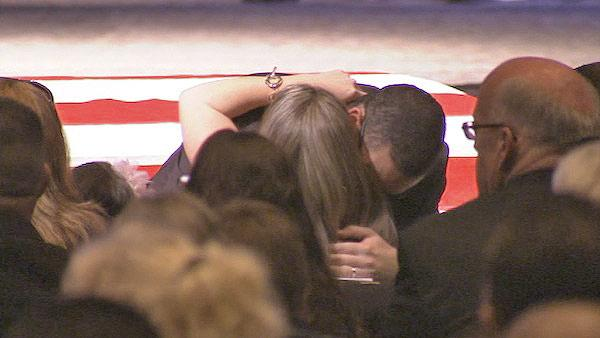 Wife Regina Crain hugs a friend during a funeral service at Grove Community Church in Riverside for Officer Michael Crain on Wednesday, Feb. 13, 2013.