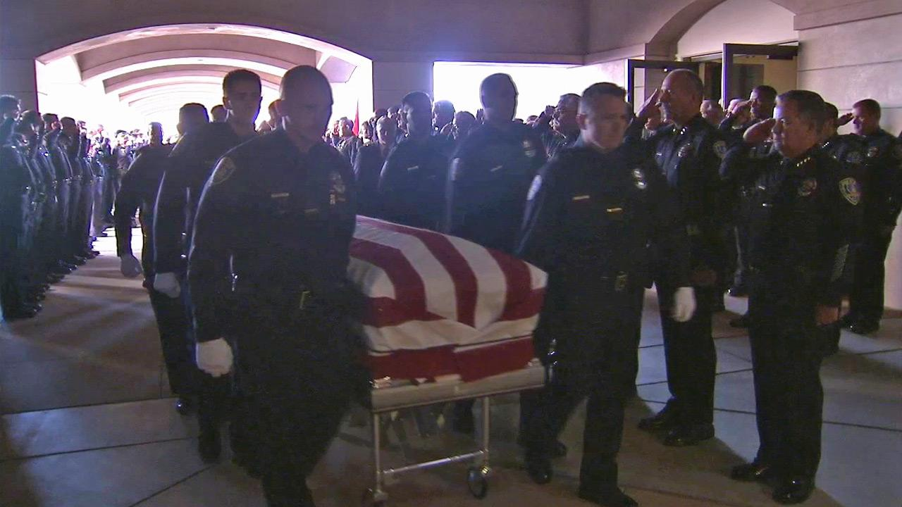 The flag-draped coffin of Riverside Officer Michael Crain is carried into Grove Community Church on Wednesday, Feb. 13, 2013. The 34-year-old was gunned down in an alleged ambush by former LAPD officer Chris Dorner on Thursday, Feb. 7, 2013.