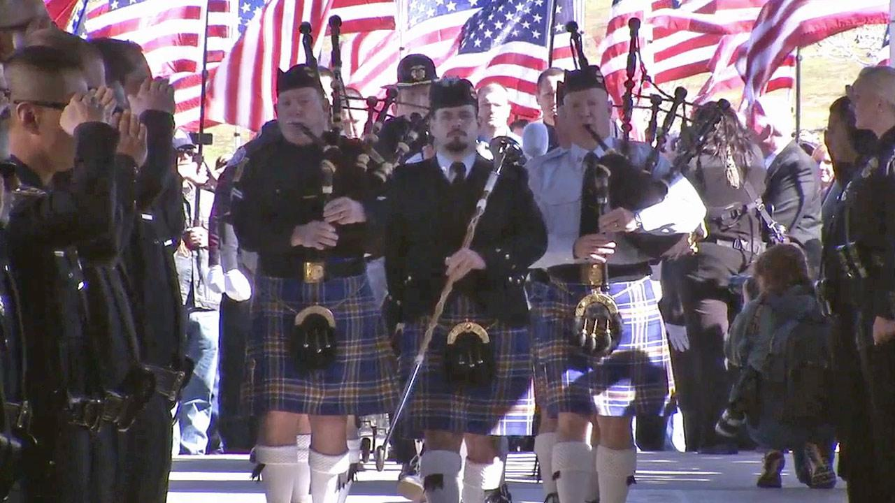A white-gloved honor guard carries the flag-draped coffin of Officer Michael Crain inside at Grove Community Church in Riverside to the sound of bagpipes on Wednesday, Feb. 13, 2013.