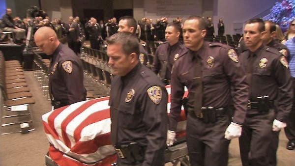 The flag-draped coffin of Riverside Officer Michael Crain is carried out of Grove Community Church on Wednesday, Feb. 13, 2013. The 34-year-old was gunned down in an alleged ambush by former LAPD officer Chris Dorner on Thursday, Feb. 7, 2013.