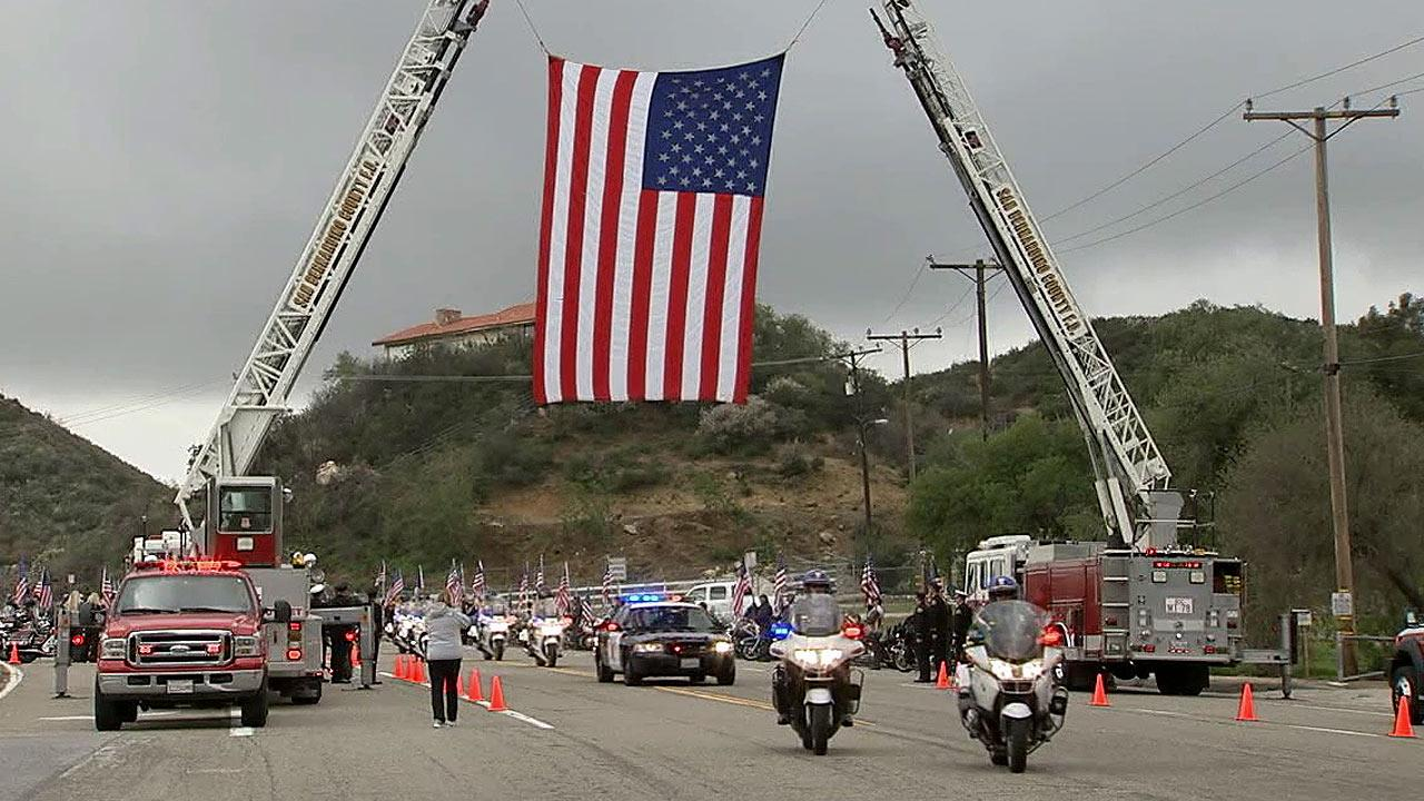 The funeral procession for San Bernardino County Sheriffs Detective Jeremiah MacKay arrives at the San Manuel Amphitheater in San Bernardino on Thursday, Feb. 21, 2013.