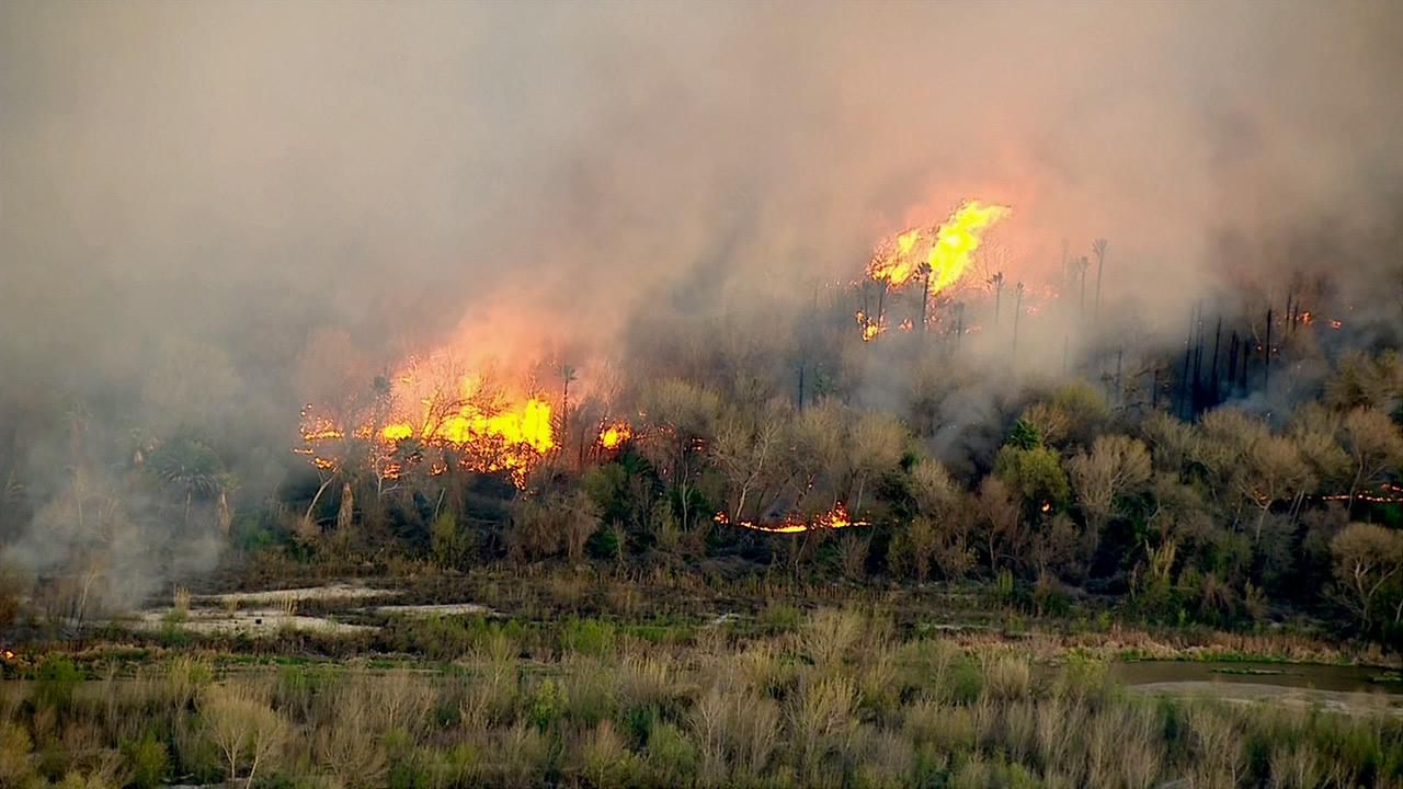 A brush fire is seen in a riverbed in Jurupa Valley on Thursday, Feb. 28, 2013.
