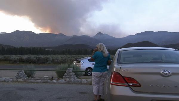 Marsha Willert of Garner Valley looks out at the smoke from the brush fire burni