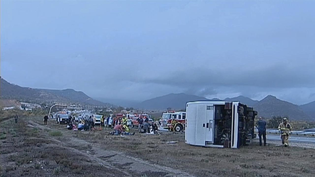 People are seen after a crash involving a tour bus and multiple vehicles on the southbound 15 Freeway near Fallbrook in San Diego County on Thursday, Dec. 19, 2013.