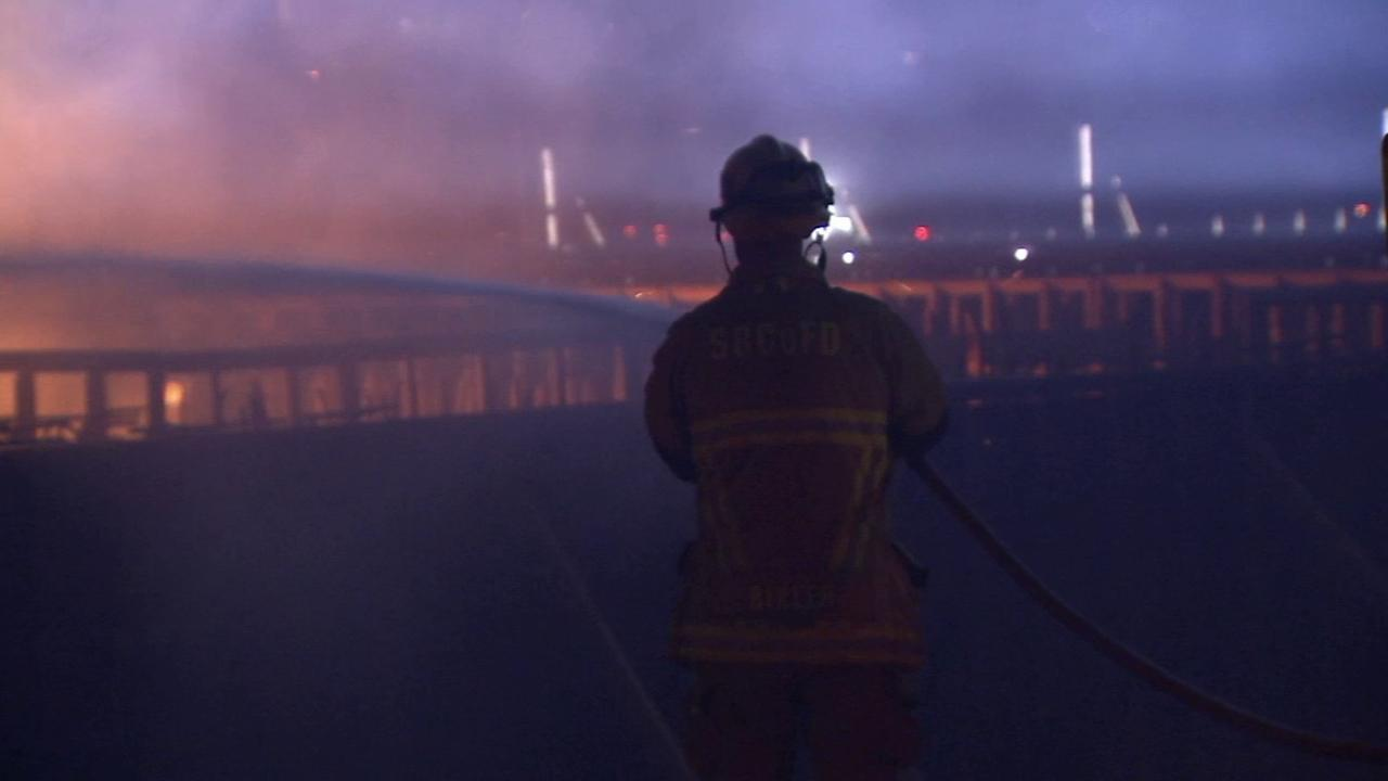 A firefighter sprays a stream of water on the Ranchero Road Bridge fire in Hesperia.