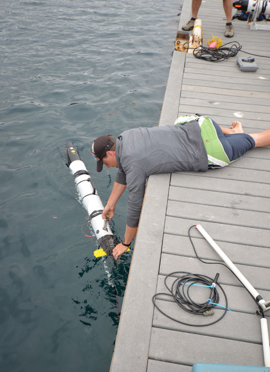 Dr. Chris Clark sets a robot into the water. The maximum speed of the robots is 4 knots. <span class=meta>(Courtesy of Dr. Gwen Goodmanlowe)</span>