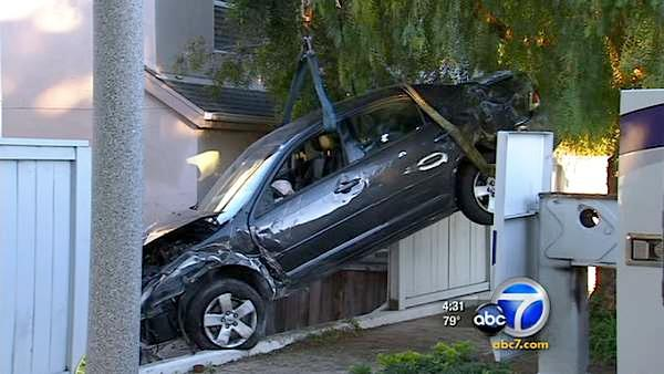 Crash wedges car between 2 homes in San Pedro