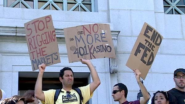 Demonstrators hold up signs outside Los Angeles City Hall during the 'Occupy LA' event, on Saturday, Oct. 1, 2011, a demonstration in solidarity of ongoing protests in New York City and other parts of the nation against corporate greed.