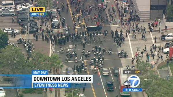 Los Angeles police officers move in on the intersection of Hill and 4th streets in downtown Los Angeles after a brief skirmish between May Day protesters and officers on Tuesday, May 1, 2012.