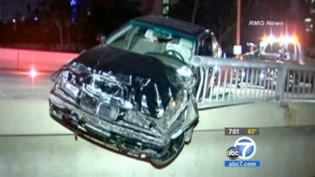 A wrecked BMW hangs over the guardrail of the Fourth Street Bridge atop the 110 Freeway in downtown Los Angeles on Sunday, June 3, 2012.