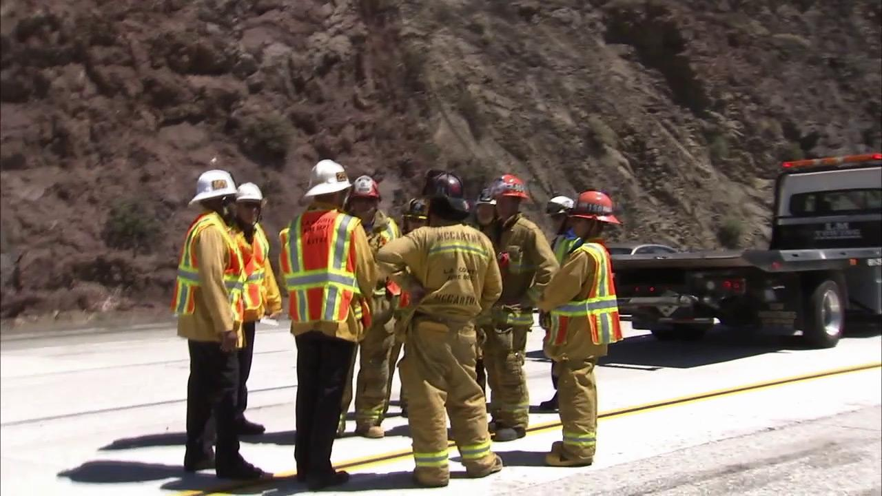 Los Angeles County Fire officials are seen next to a 19-vehicle accident on the southbound 14 Freeway in Agua Dulce on Tuesday, June 26, 2012.