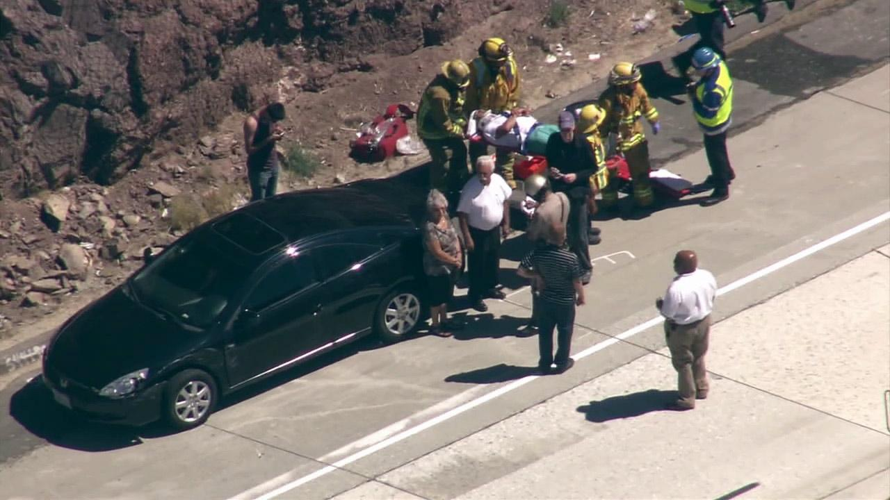 Paramedics transport an injured person after a 19-vehicle accident on the southbound 14 Freeway in Agua Dulce on Tuesday, June 26, 2012.