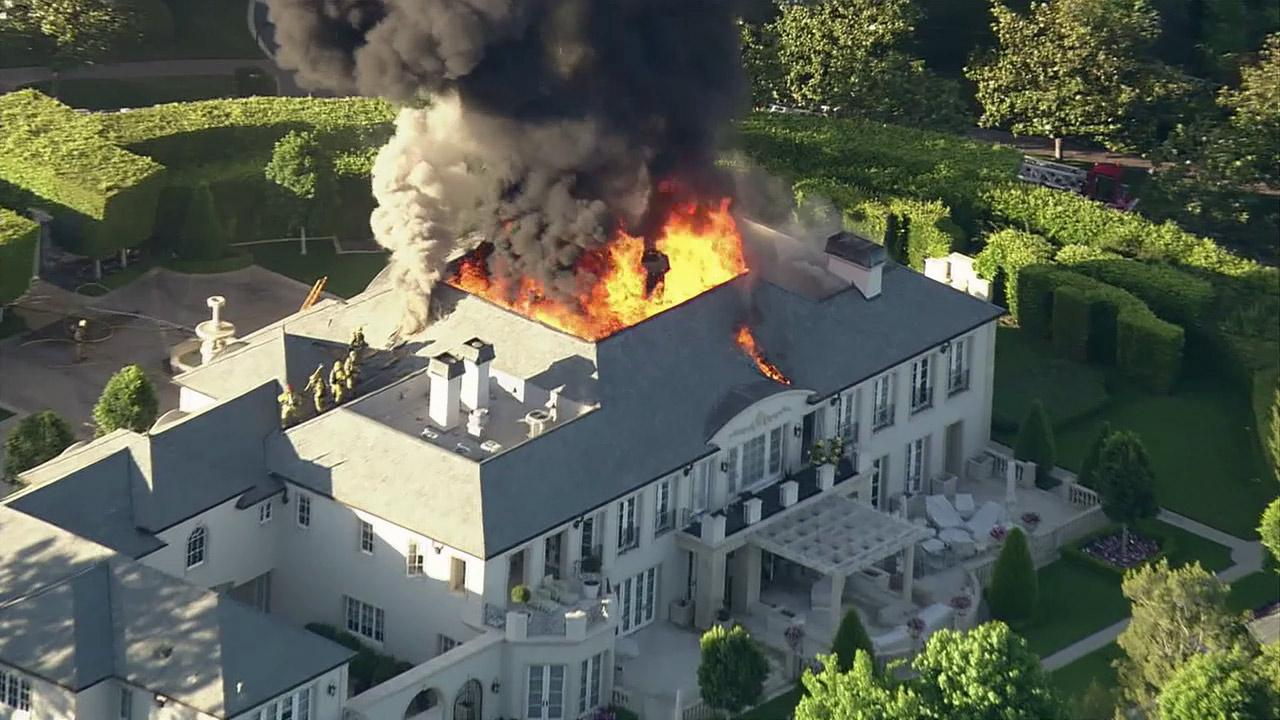 A Beverly Hills mansion, reportedly the former home of Lisa Vanderpump of The Real Housewives of Beverly Hills, is seen on fire in this photo from Friday, June 29, 2012.