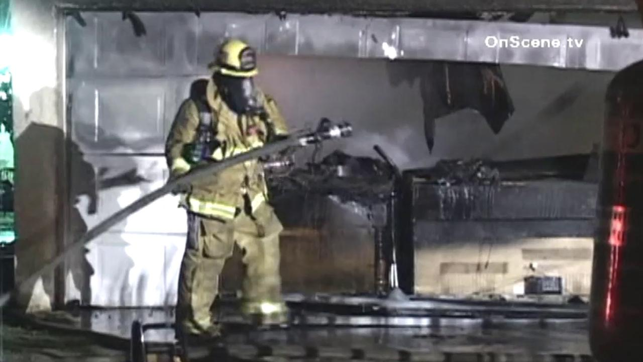 A firefighter battles a blaze at a Compton garage. Authorities say the fire was sparked by illegal fireworks.