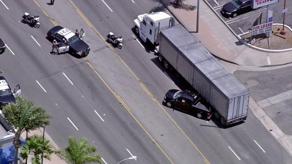 Police are seen in a standoff with a pursuit suspect, who remained inside the vehicle after crashing into a big rig on Tuesday, July 10, 2012.