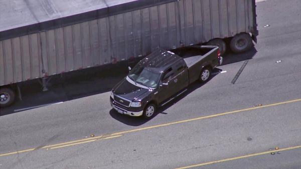 The bed of a pursuit suspect's truck is seen stuck under a big rig after the driver lost control of the vehicle following a PIT maneuver during a pursuit on Tuesday, July 10, 2012.
