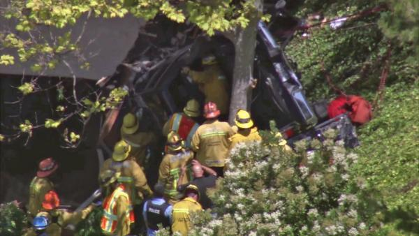 Emergency personnel and officers work to get a pursuit suspect out of his truck after the man drove off an embankment and slammed into a tree in Rolling Hills Estates during a high speed chase on Tuesday, July 10, 2012.