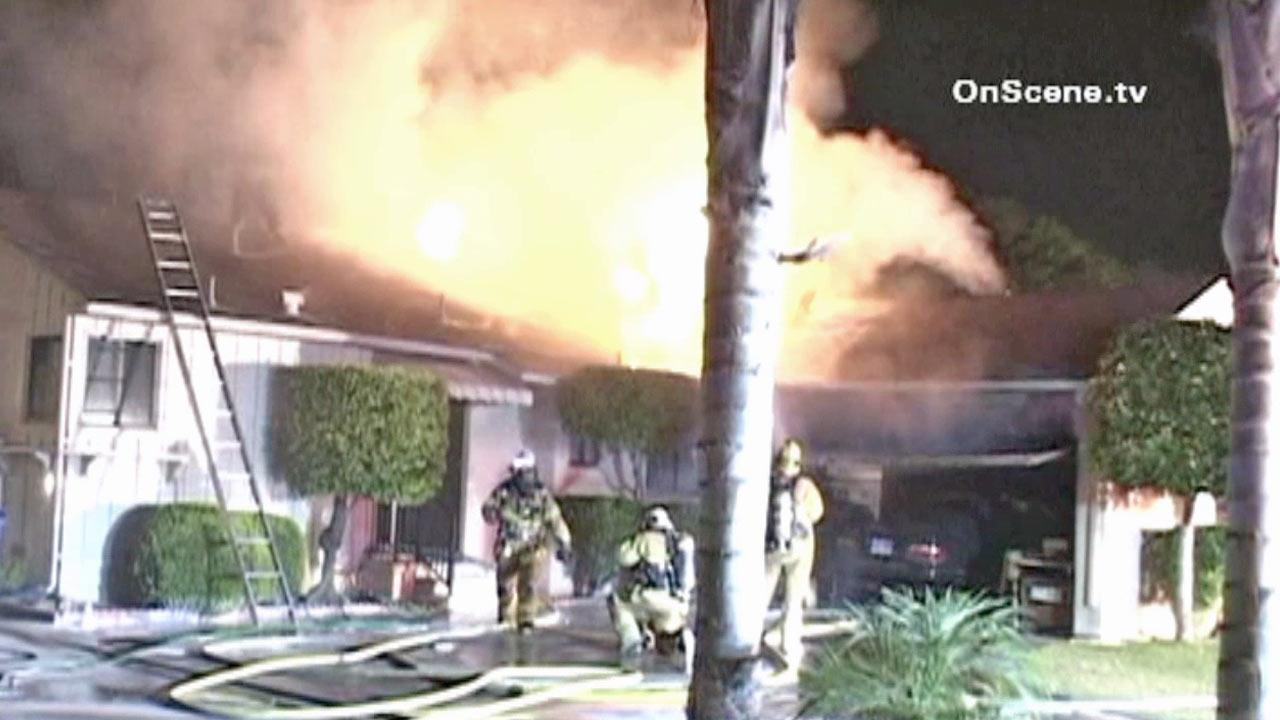 Firefighters surround the scene of a house fire in Downey on Thursday, July 12, 2012.