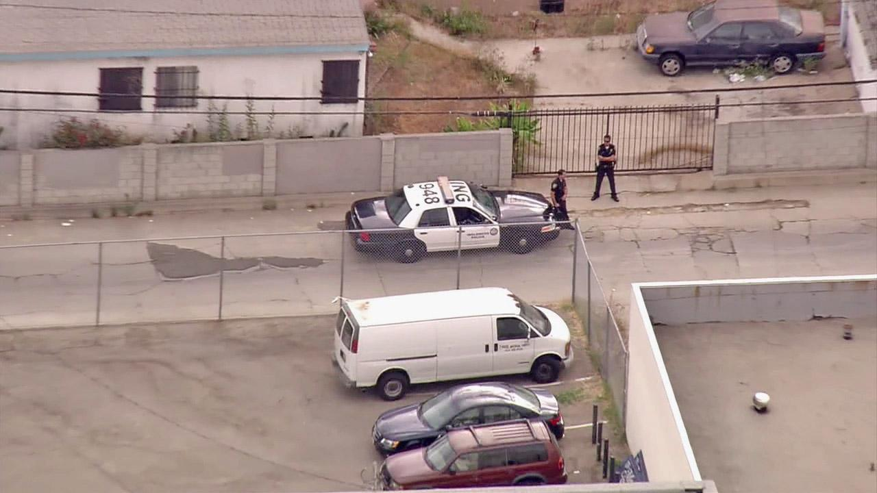 A patrol car and police officers are shown near the scene of a fatal shooting on North La Brea Avenue in Inglewood.
