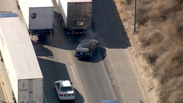 A car is seen weaving out from behind several big rigs during a pursuit near Sylmar on Fri