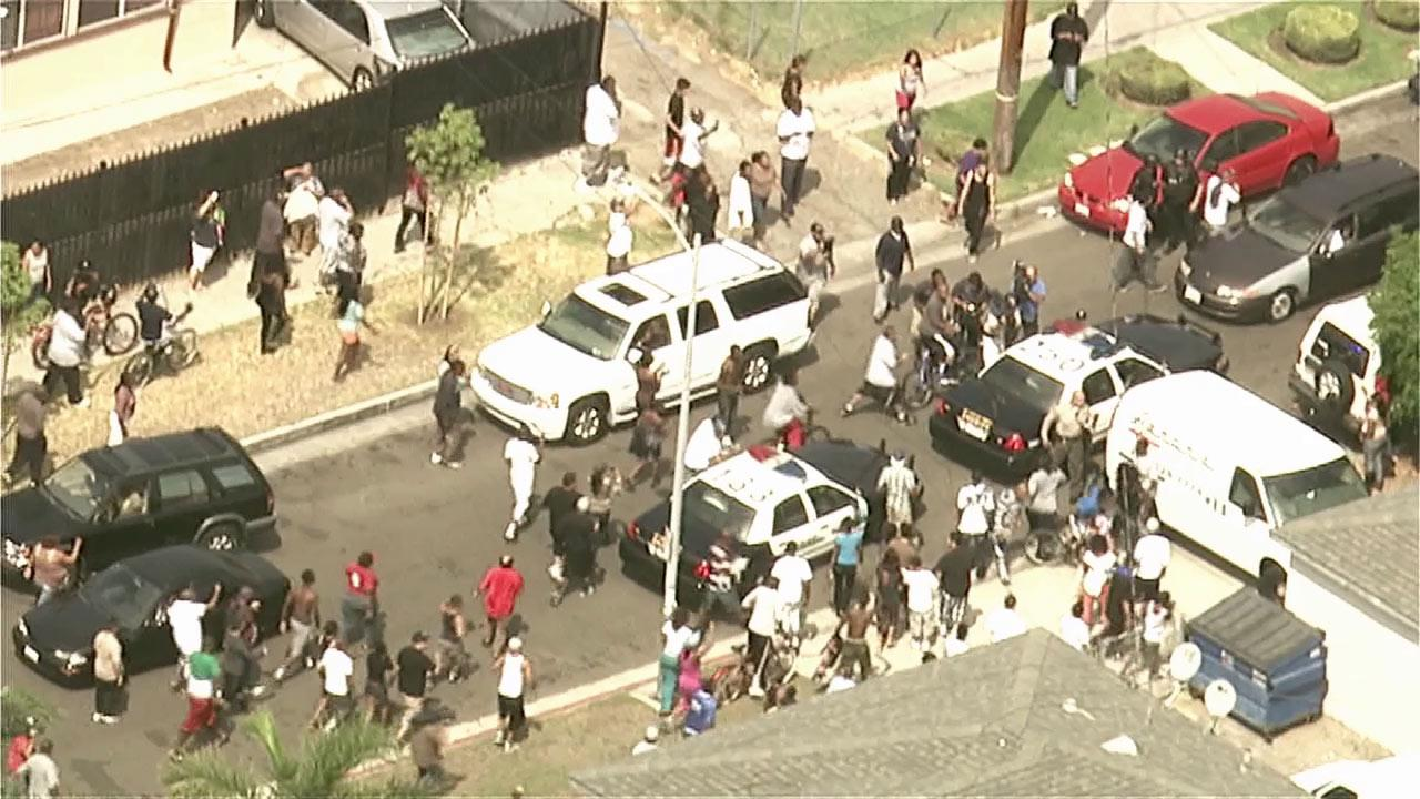 A large crowd pressed in as two bank robbery suspects were taken away after a wild chase that ended in South L.A. on Wednesday, Sept. 12, 2012.
