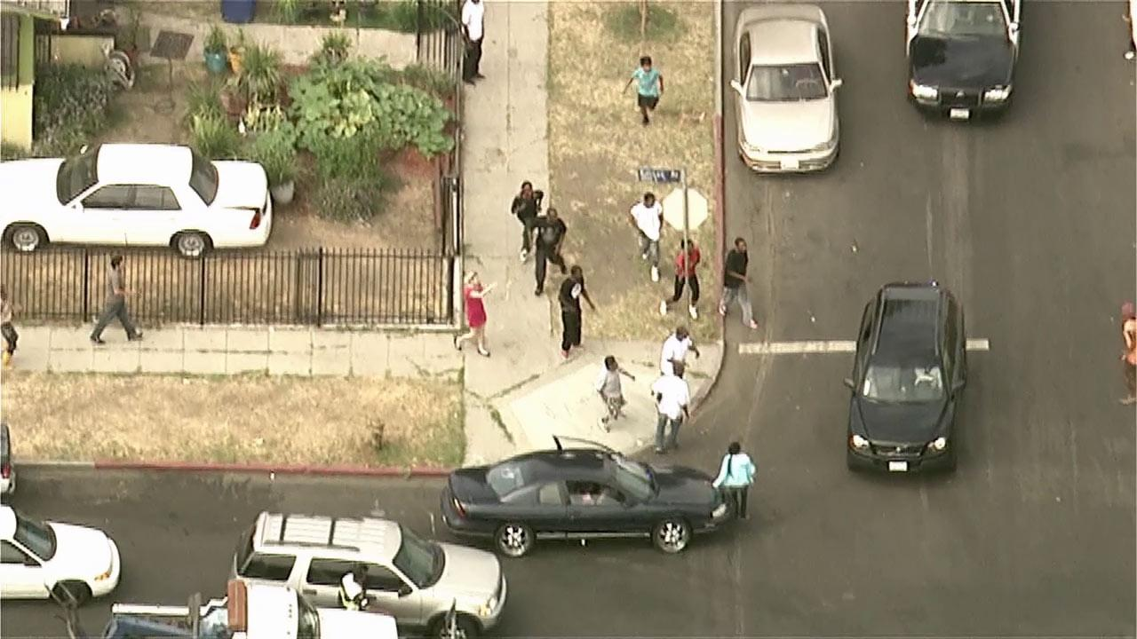 People chase after bank robbery suspects in a Volvo SUV who were seen throwing money out the windows during a pursuit in South Los Angeles on Wednesday, Sept. 12, 2012.