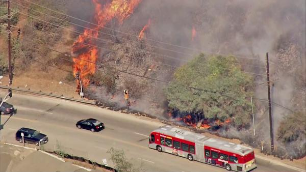 Cars are seen driving past a brush fire that erupted in the Sepulveda Pass near the 405 Freeway at Getty Center Drive on Friday, September 14, 2012.