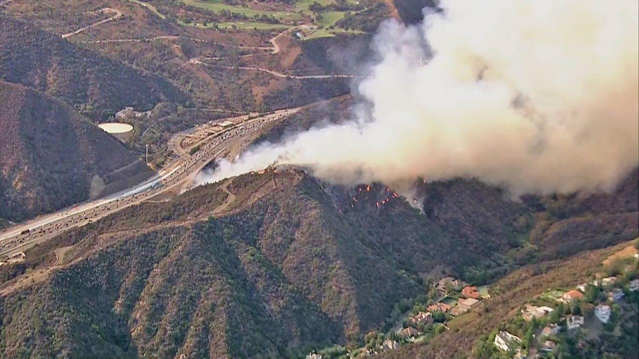 A brush fire is seen burning near homes in the Sepulveda Pass near the 405 Freeway at Getty Center Drive on Friday, September 14, 2012.