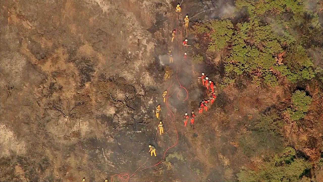 Firefighters are seen battling a blaze in the Sepulveda Pass near the 405 Freeway at Getty Center Drive on Friday, September 14, 2012.
