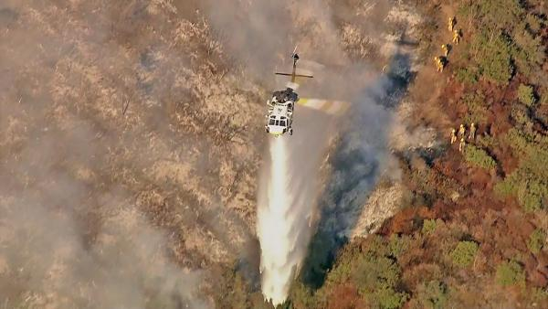 A helicopter is seen fighting a fire that burned in the Sepulveda Pass near the 405 Freeway at Getty Center drive on Friday, September 14, 2012.