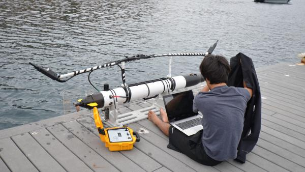 Student Dylan Shinzaki preps a robot, also known as an autonomous underwater vehicle, for its mission to track leopard sharks in Fisherman's Cove off Catalina Island in July 2012.
