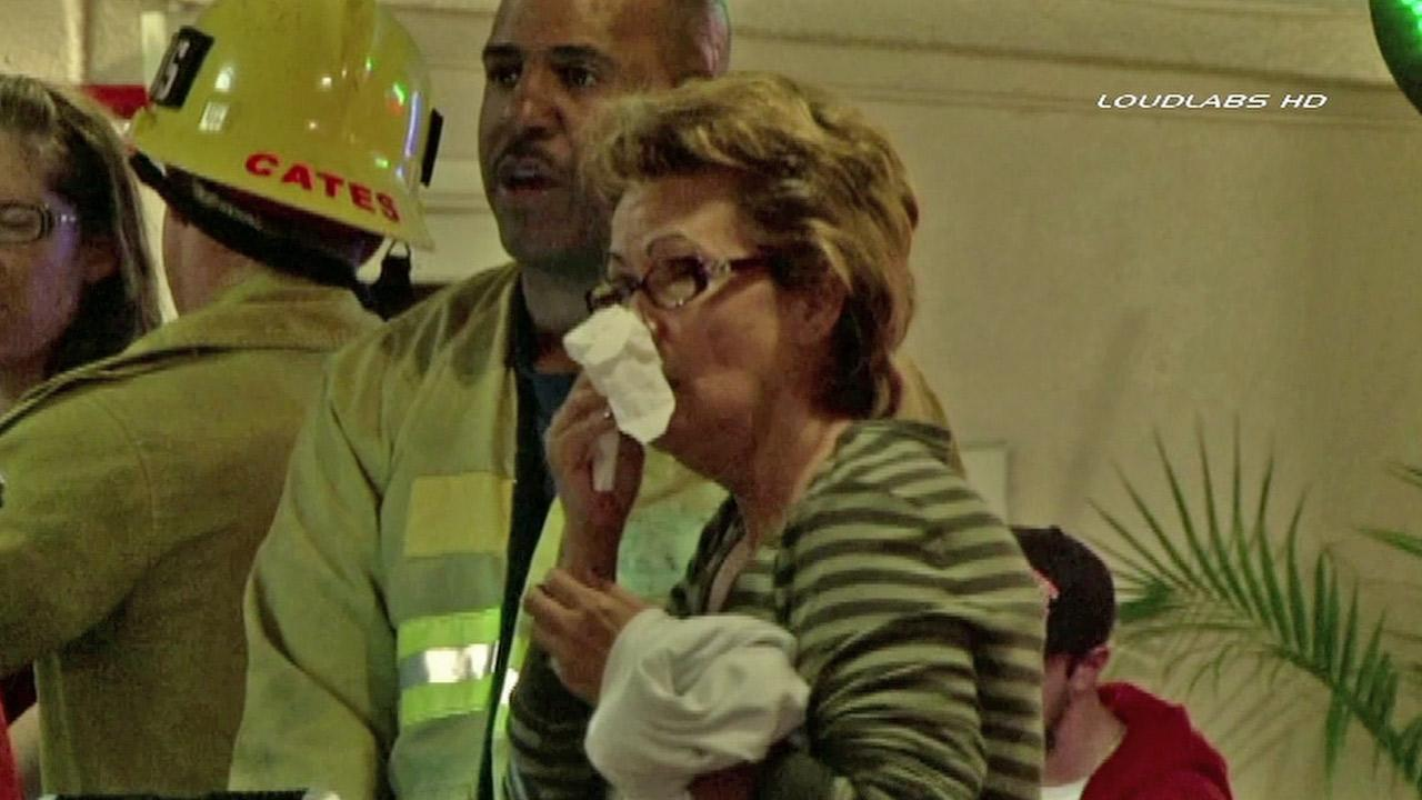 A woman covers her face after guests were evacuated from the La Quinta Inn and Suits near LAX on Saturday, Oct. 06, 2012.