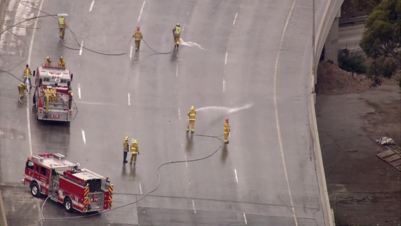 Crews hose down northbound lanes of the 101 Freeway after a lime spill created a mess on the roadway on Thursday, Oct. 18, 2012.