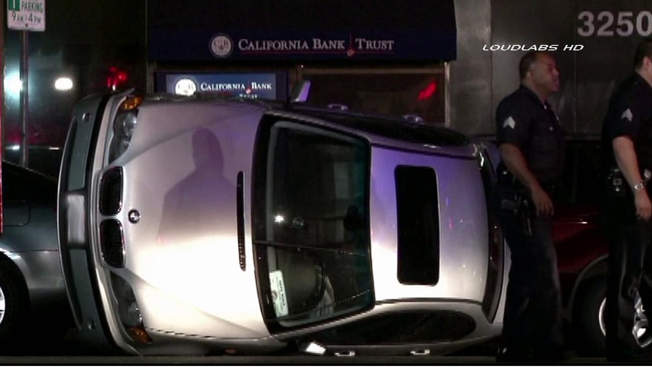 A car appears flipped on its side following a police pursuit in Koreatown on Friday, Oct. 26, 2012.