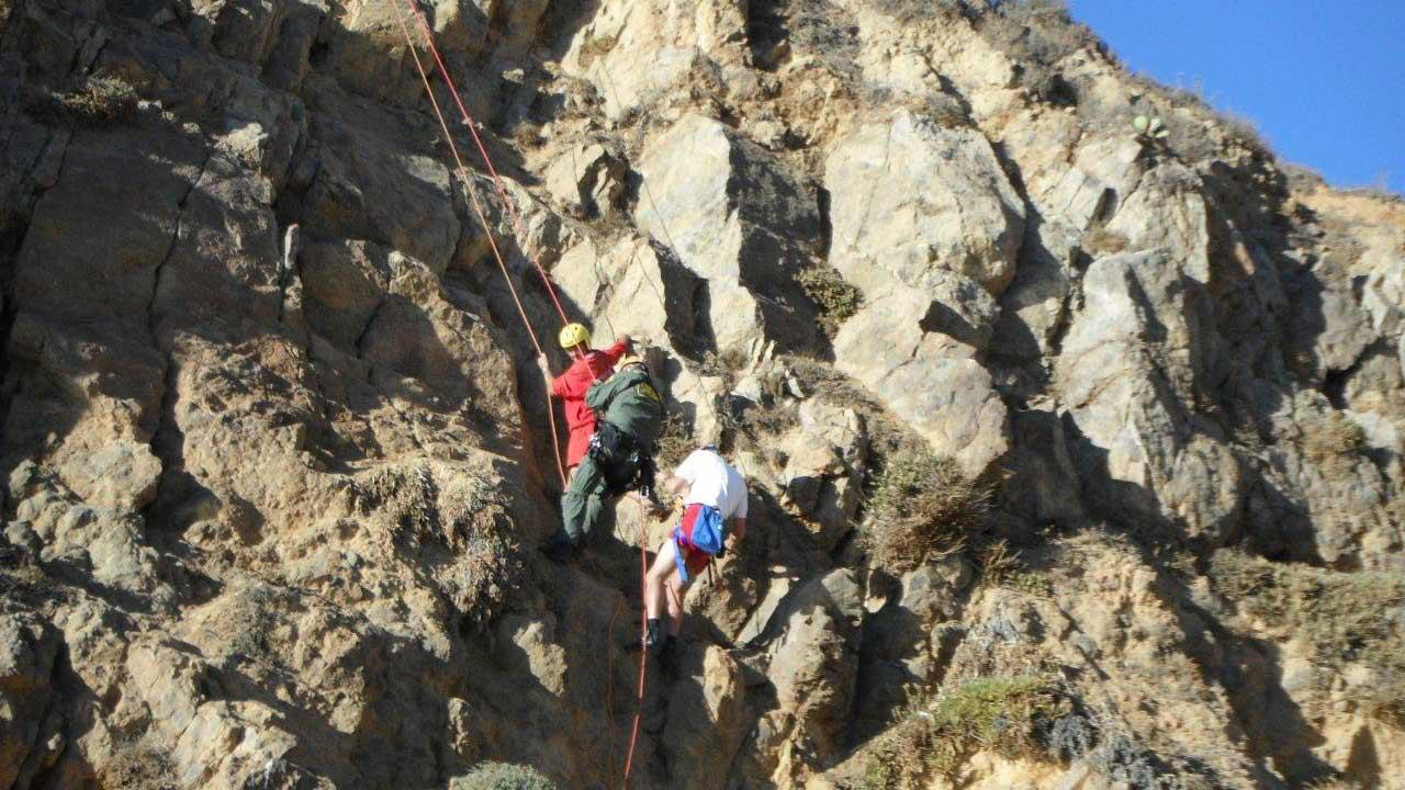 Two lifeguards who attempted to save a woman stranded 50-feet above rocks in Pirate Cove ended up getting rescued by the LA County Sheriffs Malibu Search and Rescue Team Saturday, Oct. 27, 2012.