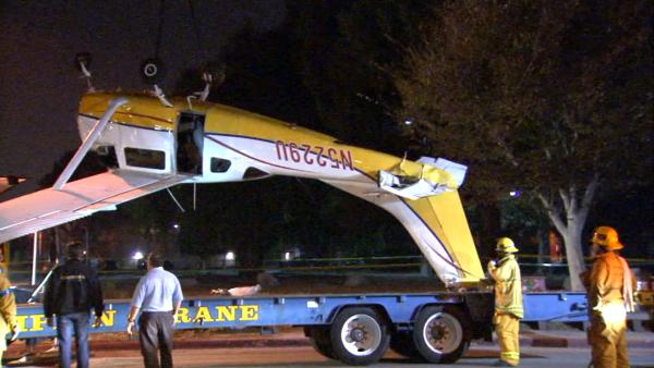 A small plane is hauled off after crashing on the California State University, Northridge, campus on Su
