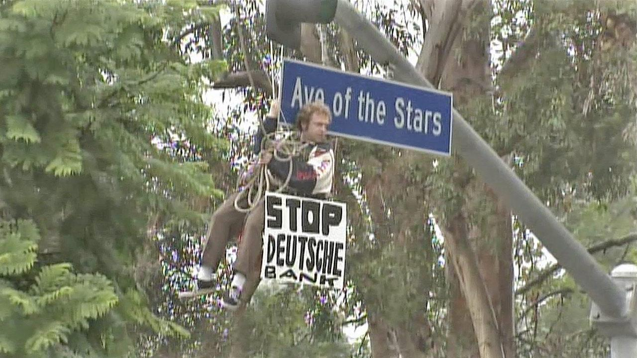 A protester dangles from an overhead traffic light on Avenue of the Stars in Century City on Thursday, Nov. 29, 2012.