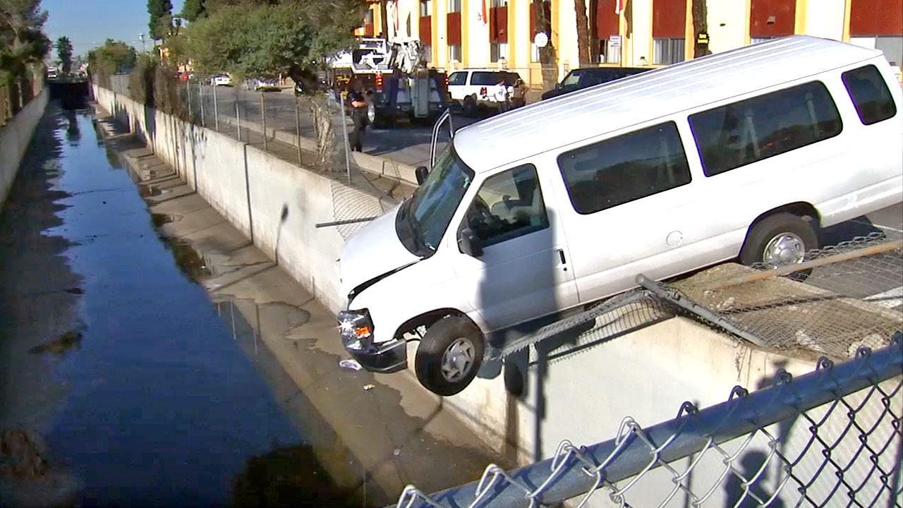 A van carrying a youth group crashed through a fence and dangled from the wall of a wash in North Hills on Saturday, Dec. 8, 2012.