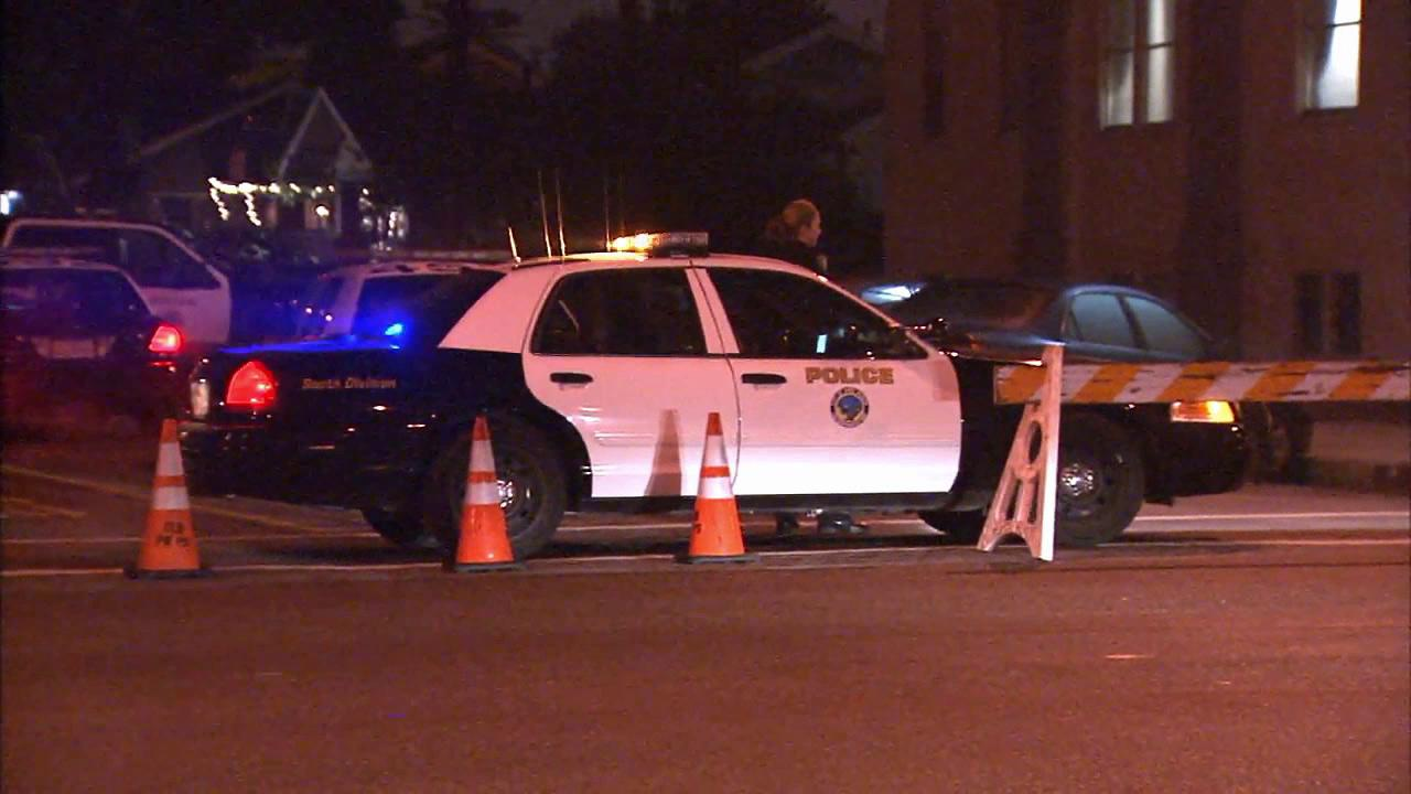 A police vehicle parks in an area blocked off for a suspect search in Long Beach on Sunday, Dec. 9, 2012.