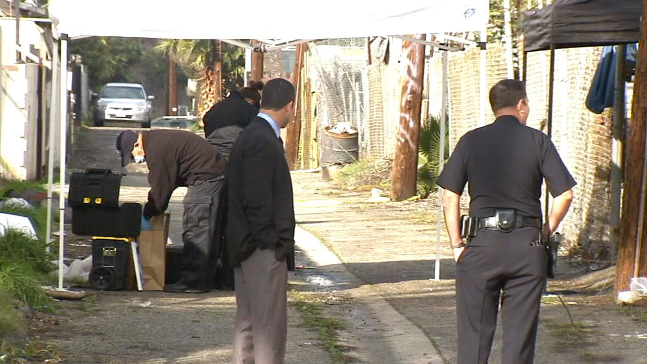 Investigators work in an alley behind where a home went up in flames on Monday, Dec. 24, 2012.