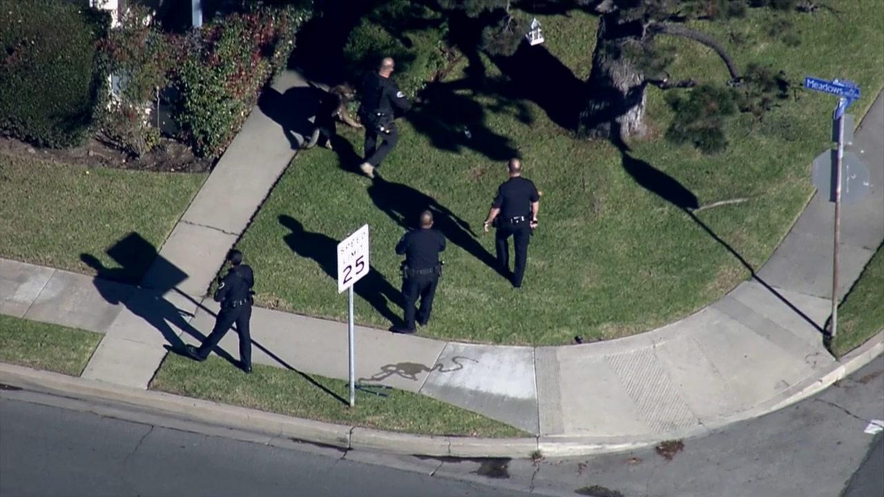 Police search for burglary suspects in a Manhattan Beach neighborhood on Tuesday, Jan. 15, 2013.