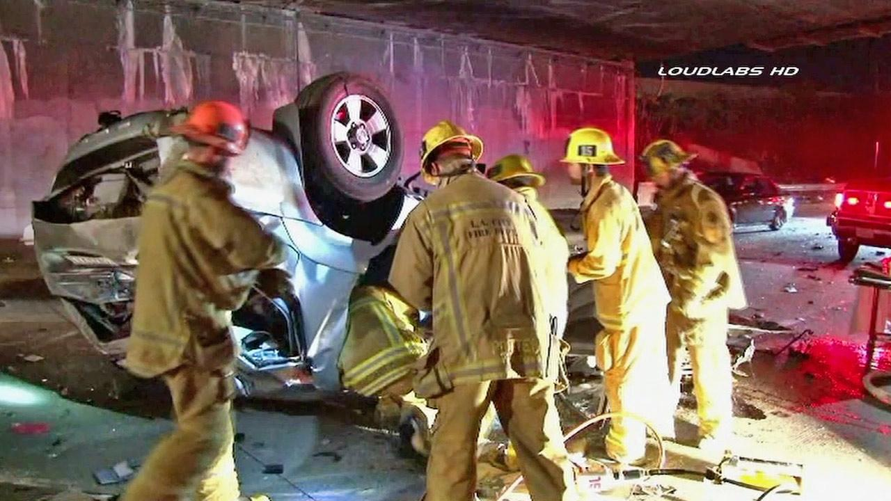 An emergency crew surrounds a car involved in a crash on the northbound lanes of the 110 Freeway in Los Angeles on Sunday, Jan. 20, 2013.